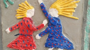 Clay mural of two blond girls in red and blue polka dot dresses dancing exuberantly, hair streaming out behind them.