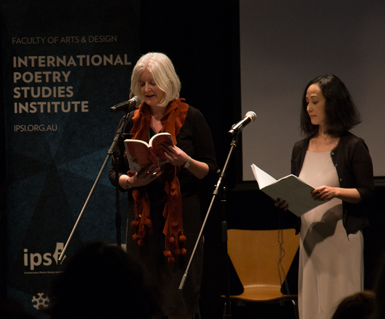 Melinda Smith (right) and Harumi Kawaguchi (left) reading in front of microphones.