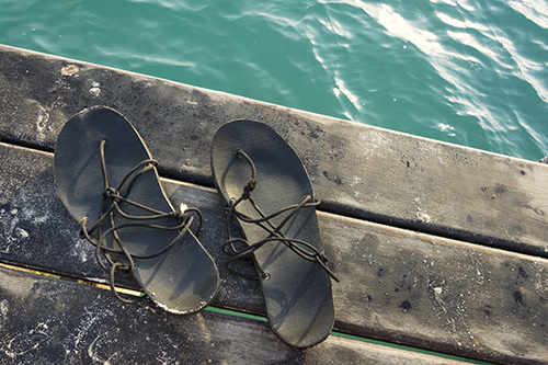 Two worn-out sandals on a wooden pier with green water.