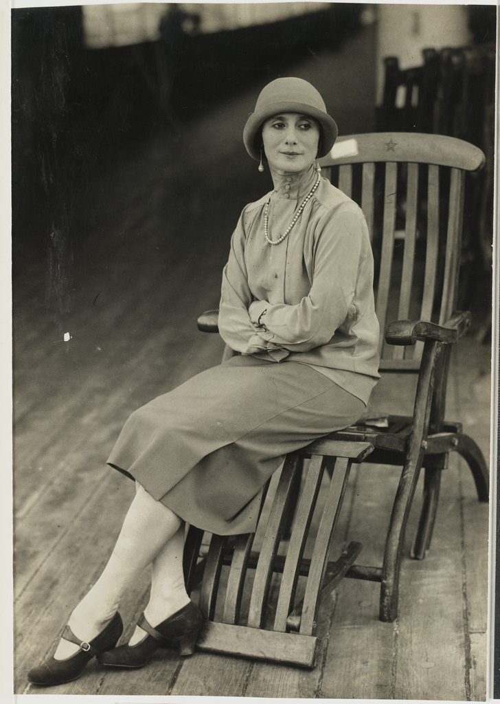 Anna Pavlova sitting very still on a deck chair.