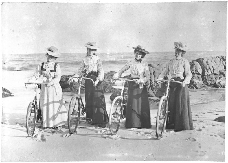 Four women on a beach with bicycles.