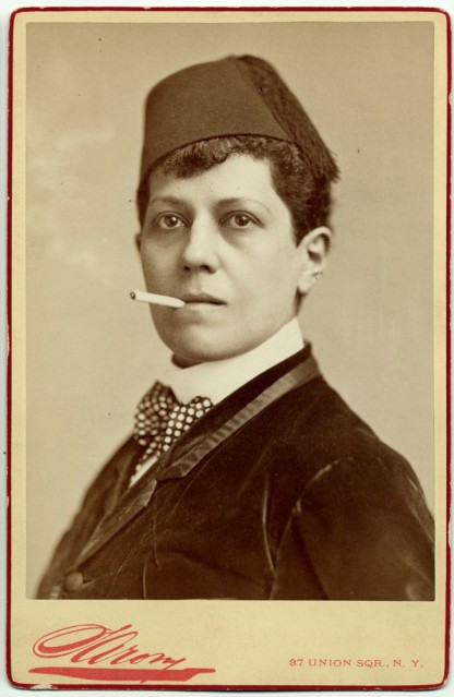 Woman dressed in a fez with a cigarette.