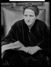 Gertrude Stein seated, arms crossed.
