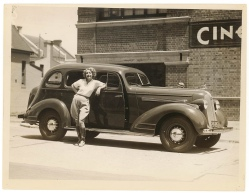Woman leaning casually against a car.