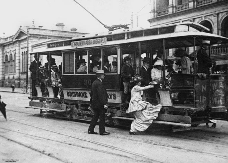 Woman in a very long dress struggling to board a tram.