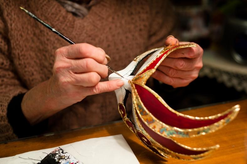 Woman creating a Venetian festival mask.